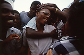 Port-au-Prince, Haiti.August 23, 1987..The dearly loved opposition leader Father Jean-Bertrand Aristide is embraced by a crowd prior to elections being held on November 29th, the first attempt at a democratic election in Haiti. It was unsuccessful as 34 people were killed at a polling station and elections were moved up to February 1988...Leslie François Manigat won the election with many political parties boycotting. He had military backing but once in office he sought greater control over the military in an effort, to fight corruption. Manigat's government was overthrown by General Henri Namphy within months.