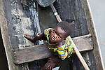 A young girl in Ganvie sits in a boat, looking up at the camera.  Ganvie, Benin, with some 3,000 stilted buildings and a population of 20,000-30,000 people, may be the largest &quot;lake vllage&quot; in Africa.  In Ganvie, the population lives exclusively from fishing, building houses on stilts in and next to Lake Nokoue.  Because the Dan-Homey religion prohibited attacks on communities living in the water, the village of Ganvie dates back to the 16th or 17th century, when it was built to protect people from slavery.  Even Ganvie's fruit and vegetable market is on water!!!