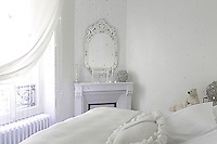 "In contrast to the rest of the house this bedroom, called the ""Reine des Neiges"",  is painted in icy tones of white with Swarovski crystal pendants hanging in the window to add to the wintry atmosphere"