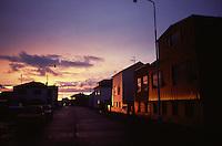 Islanda: paesaggio urbano. Un villaggio all'alba. Palazzi bassi e automobili parcheggiate. Nessuno in strada.