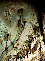 STALACTITES &amp; STALAGMITES <br /> Drapery in limestone cavern<br /> Calcium carbonate deposits (Stalactites) hang from the top of limestone caverns, formed by the dripping of mineralized solutions. Corresponding columnar deposits (Stalagmites) are built upward. Papoose Room, Carlsbad.