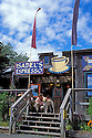 Isabel's Espresso cafe in Lopez Village, with woman and dog on steps; Lopez Island, San Juan Islands, Washington.