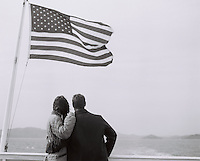 couple on a ferry boat with an American flag flying in San Francisco
