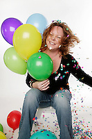 Adult woman photo in studio celebrating with balloons and confetti.
