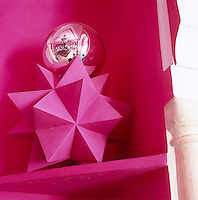 With a bauble on top and painted to match, a painted polyhedron sits on the shelf of a shocking-pink recess