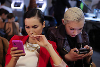 Mexico City, Mexico. 4rd April 2014 - Models check their mobile phones  at backstage during the Mercedes-Benz Fashion Week in Mexico. Photo by Miguel Angel Pantaleon