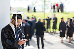 Nick Sander, an audio production major, checks his phone before the start of the morning Undergraduate Commencement ceremony on Saturday, May 2, 2015.  Photo by Ohio University  /  Rob Hardin