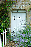 Lavender bush and traditional cottage entrance in the Cotswolds village of Bledington, Oxfordshire, UK