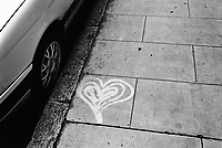 Switzerland. Canton Geneva. Geneva. Graffiti with a heart on the side walk. A car is parked in the street. 23.10.02  © 2002 Didier Ruef
