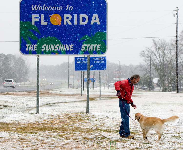 man plays with his dog in the snow in Florida on US 231 at the