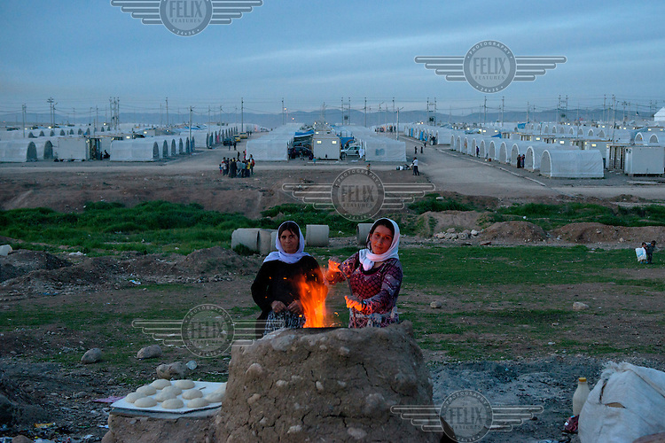 Two Yazidi refugee women make bread in a refugee camp in Dohuk, Iraq.<br /> Thousands of Yazidis fled their homes when Islamic State (IS) attacked Yazidi towns and villages in August 2014. Many are now living in refugee camps.