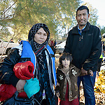 An Afghan refugee family stands on a beach near Molyvos, on the Greek island of Lesbos, on November 2, 2015, after crossing the Aegean Sea from Turkey. Local and international volunteers welcomed the arriving refugees with food and medical care and dry clothes before the newcomers proceeded on their way toward western Europe. Their boat to Greece was provided by Turkish traffickers to whom the refugees paid huge sums to arrive in Greece.