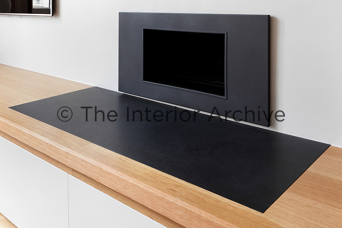 A detail of a contemporary fireplace and hearth set in a wooden unit.