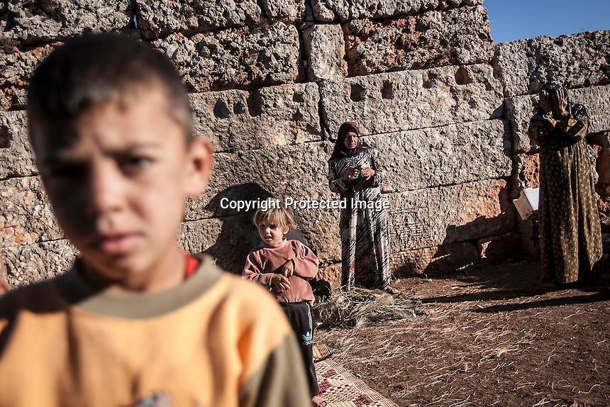 "In this Friday, Sep. 27, 2013 photo, a Syrian displaced women cook a meal for breakfast as children play in the ground at the Kafr Ruma, an ancient roman ruins used as temporary shelter by those families who have fled from the heavy fighting and shelling in the Idlib province countryside of Syria. Dozens of families settled in the ancient ruins known as ""The Forgotten City"" and declared human heritage by UNESCO, when the clashes between opposition fighters and government forces broke out in the region since more than two years ago. (AP Photo)"