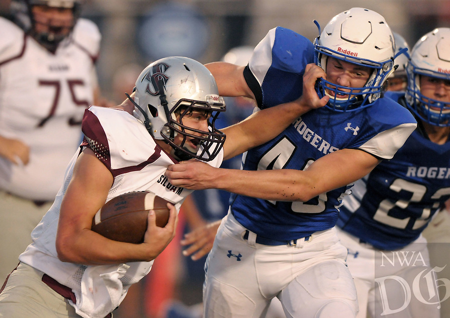 Luke Lampton, Siloam Springs quarterback, pushes off Gary Fredrick, Rogers linebacker, on Friday Sept. 2, 2016 during the second quarter of the game at Whitey Smith Stadium in Rogers.