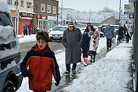 Pedestrians walking along a snowy pavement, past local shops.