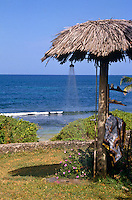 An outdoor shower under a decaying thatched roof with a view of the ocean