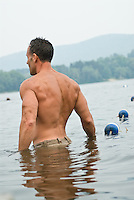 Back of shirtess man  walking into the swimming area  in a  lake /in the Berkshires