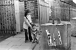Derry Northern Ireland Londonderry. 1979. Young mother at Butchers Gate with son. Torn poster for Bernadette Devlin, who was elected as a Member of Parliament for