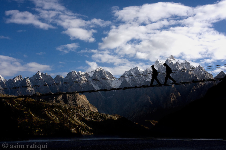 A rickety suspension bridge connects two sides of a Hunza valley near the village of Gulmith, with the imposing peaks of The Cathedral in the background.