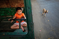 A boy plays with an abandoned tractor as a dog passes by in historical central Yangon April 12, 2012. Myanmar, also known as Burma, was a British colony until winning its independence in 1948 thanks to the late national hero General Aung San, the father of democracy icon Aung San Suu Kyi. Yangon, also known as Rangoon, was the capital of British Burma and a major port between Calcutta and Singapore. It owes its current appearance to British planners, with streets laid out in a grid, interspersed with churches, temples and grand but neglected municipal buildings. British Prime Minister David Cameron will push for more reforms during a landmark visit to Myanmar later on Friday, the first by a major Western leader in 50 years as countries jockey for business and influence in the long isolated state.  REUTERS/Damir Sagolj (MYANMAR)