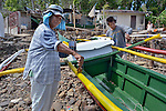 Ninfa Necesario paints a boat that her son Joel (right) has rebuilt following the destruction caused in the Philippines by Typhoon Haiyan in November 2013. They live on Manipulon, a small island off the coast from the town of Estancia. The storm was known locally as Yolanda. Residents of this island have received assistance from the ACT Alliance. Most of the island's boats were damaged or destroyed by the typhoon and its brutal storm surge.