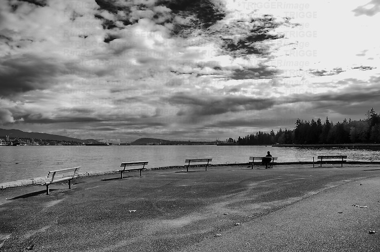 Lone man siting on a curved row of park benches overlooking ocean, clouds, mountains and industry.