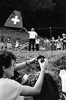 Switzerland. Canton Uri. Rütli feld. 1 August 1990. Swiss national holiday. Public holiday. A man throws a swiss flag in the air. Other men play the traditional Alp horn. A group of women wear national traditional costumes. A mother puts on her son's head a hat with edelweiss flowers. Rütli is the birthplace of the Swiss Confederation.  © 1990 Didier Ruef