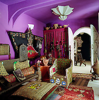 The purple-painted living room is furnished with an eclectic mix of ethnic furniture and artefacts