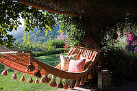 A comfortable hammock hanging under the covered terrace is positioned to make the most of the spectacular view of the lush garden and to capture the evening sun