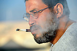 A wounded veteran of armed struggle against the Libyan government, this man smokes a cigarette in the Zaatari Refugee Camp, located near Mafraq, Jordan. Opened in July, 2012, the camp holds upwards of 50,000 refugees from the civil war inside Syria, but its numbers are growing. International Orthodox Christian Charities and other members of the ACT Alliance are active in the camp providing essential items and services.