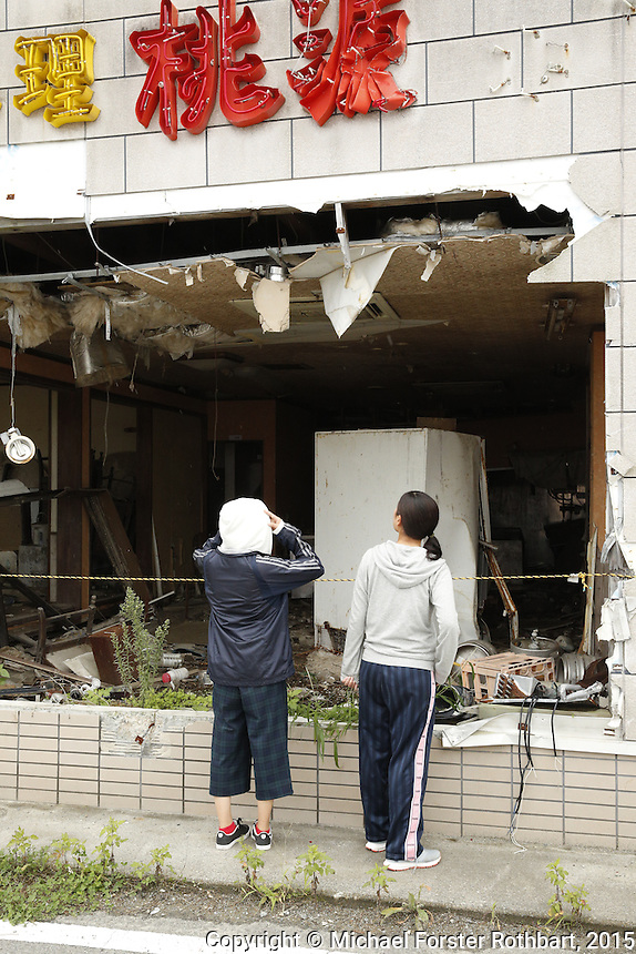 In Tomioka, Japan, buildings and cars destroyed by the March 11, 2011 tsunami remain standing in the neighborhood near the former Tomioka train station. In 2015, four and a half years after the Fukushima Daiichi nuclear power plant disaster, tourists and former residents come to see the damage while laborers work nearby to decontaminate homes and commercial properties before demolition. Almost all developed properties in Tomioka are now getting cleaned or demolished. Full caption to come.<br /> &copy; Michael Forster Rothbart Photography<br /> www.mfrphoto.com &bull; 607-267-4893<br /> 34 Spruce St, Oneonta, NY 13820<br /> 86 Three Mile Pond Rd, Vassalboro, ME 04989<br /> info@mfrphoto.com<br /> Photo by: Michael Forster Rothbart<br /> Date:  9/18/2015<br /> File#:  Canon &mdash; Canon EOS 5D Mark III digital camera frame B14716