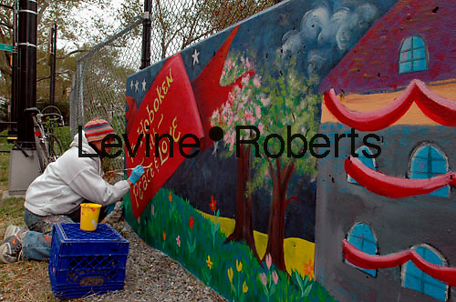 Stephanie Ashby, mural organizer,  puts finishing touches on The Hoboken Community Mural Project, painted on the retaining wall of the Little League Field. Stevens Park, Hoboken, New Jersey on October  27, 2005.  The mural celebrates Hoboken's 150th Anniversary.  it will be dedicated October 29, 2005. (© Frances M. Roberts)