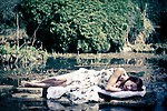 Young woman sleeping in summer dress near to water