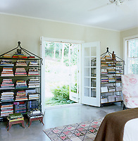 In the master bedroom a pair of wrought iron pagoda-shaped bookcases flank open French windows leading to the garden