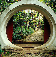 A circular doorway in concrete reveals one of a series of symbolic ruins created in the garden by Edward James
