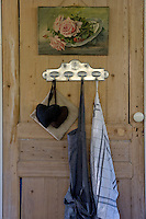 On the scrubbed and sanded pine door in the kitchen an unframed still life hangs above an antique metal rack