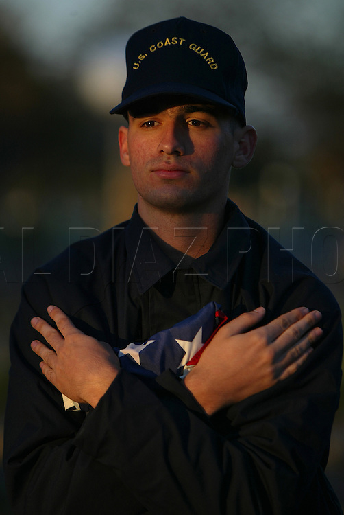 A seaman recruit embrasses the American Flag at sunrise during boot camp at The United States Coast Guard Training Center, Cape May, NJ.