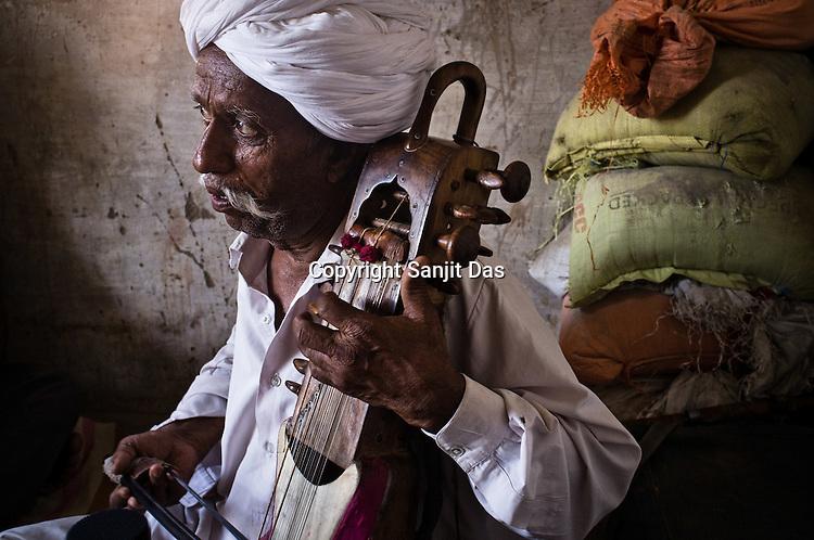 66-year-old Manganiyar artist, Lakha Khan plays the Sarangi in his house in Raneri village of Jodhpur district in Rajasthan, India. Photo: Sanjit Das/Panos