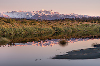 Sunset reflections of Southern Alps with Mt. Tasman and Aoraki, Mt. Cook from Three Mile beach near Okarito, Westland Tai Poutini National Park, West Coast, UNESCO Wolrd Heritage Area, New Zealand, NZ