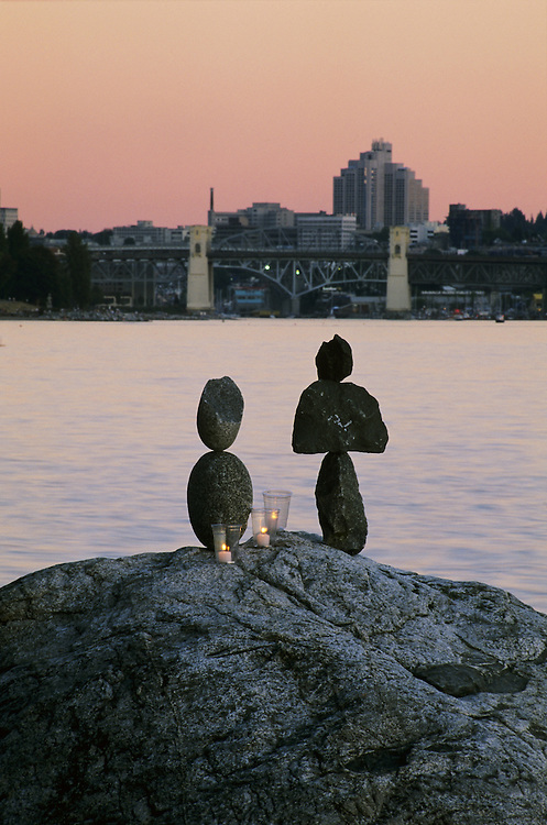 Stone pile sculpture and candles by Kent Avery, with Burrard Bridge in background, from the seawall in Stanley Park, Vancouver, BC.
