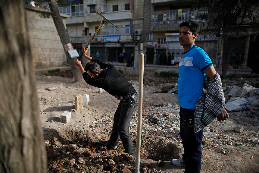 "Hisham (at left) and Free Syria Army civilian volunteers prepare a body for burial at Martyr's park (formerly known as Cobbler's Park) in the Bustan Al-Qasr neighborhood of Aleppo. ..The park, under Free Syria Army control,  has been renamed ""Martyr's Park""  since the revolution arrived in Aleppo in July of 2012.  A patch of dirt that lies next to children's swings, slides and monkey bars now serves as this neighborhood's makeshift cemetery. On January 29, 2011, 110 bodies floated down a water canal (which is part of the river Qweiq) that separates this rebel-controlled area from the regime side on the opposite side of the canal. Many of the showed signs of torture and most where executed with their hands bound behind their backs. In the weeks after this incident, dozens more bodies have been discovered in the canal - many of the victims that have not been claimed by family members have been buried here."