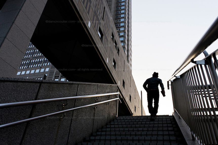 A man in silhouette ascends some steps near part of the Tokyo Metropolitan Government Building in Shinjuku, Tokyo, Japan. Friday January 21st 2011