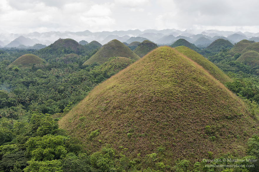Carmen, Bohol, Philippines; Chocolate Hills geological formation are grass covered limestone/basalt domes that turn brown in the dry season and look like chocolate kisses, thus giving them their name, estimated to be from 1,268 to about 1,776 individual mounds, they range in height from 30 to 50 meters to 120 meters or 98 to 164 to 390 feet