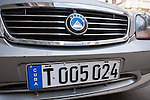 Havana, Cuba; a blue and white Cuban license plate on the front of a silver, Chinese built, Geely car