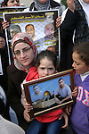 Relatives of Palestinian prisoners jailed in Israeli prisons hold their portraits during a protest in front of Red Cross office in Jerusalem, on 28 February 2013, in support of Palestinian prisoners on hunger strike. Photo by Mahfouz Abu Turk