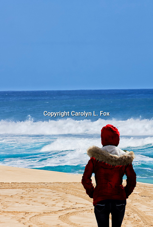 A woman wearing a red coat and a red stocking cap walks on the beach.