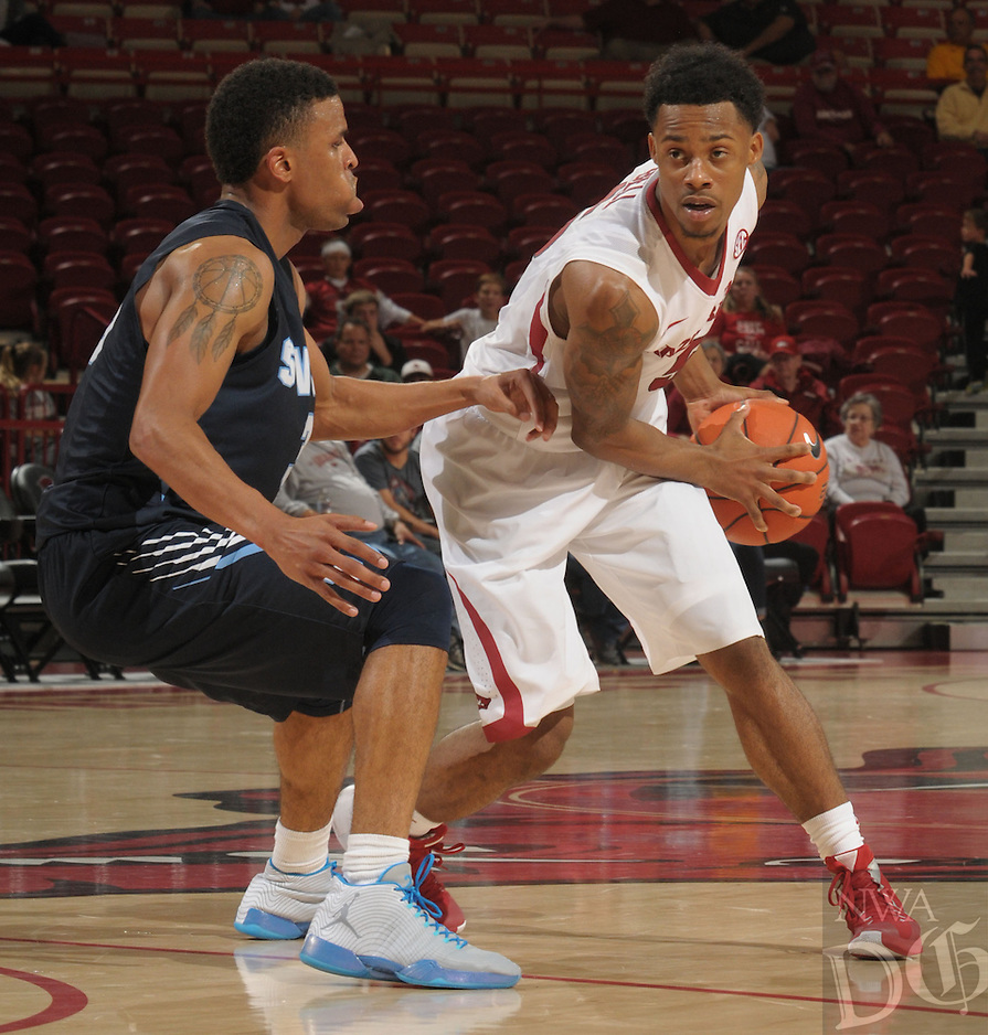 NWA Democrat-Gazette/ANDY SHUPE<br /> Anthlon Bell (right) of Arkansas looks to drive around Emeche Wells of Southwestern Oklahoma State Thursday, Nov. 5, 2015, during the second half in Bud Walton Arena. Visit nwadg.com/photos to see more photographs from the game.