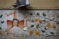 Detail of a painting on the wall of an old shop depicting the Emblem of Sicily, in Ortigia, Syracuse, Sicily, pictured on September 13, 2009, in the morning. The island Ortigia is the historic centre of Syracuse. This Triskelion emblem (a motif of three interlocked spirals) is the centrepiece of the flag of Sicily. It features the winged head of Medusa and three wheat ears. The three legs represent the triangular shape of the island of Sicily. Today the city is a UNESCO World Heritage Site. Picture by Manuel Cohen.