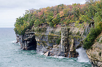 An early autumn view of the impressive Pictured Rocks shoreline with a Lake Superior wave crashing into the rocky shore. Munising, MI